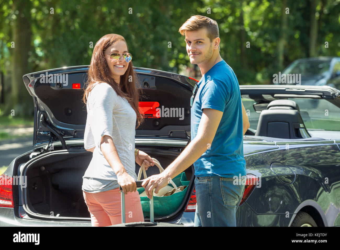 Portrait Of Young Happy Couple Putting Luggage In A Car Trunk - Stock Image