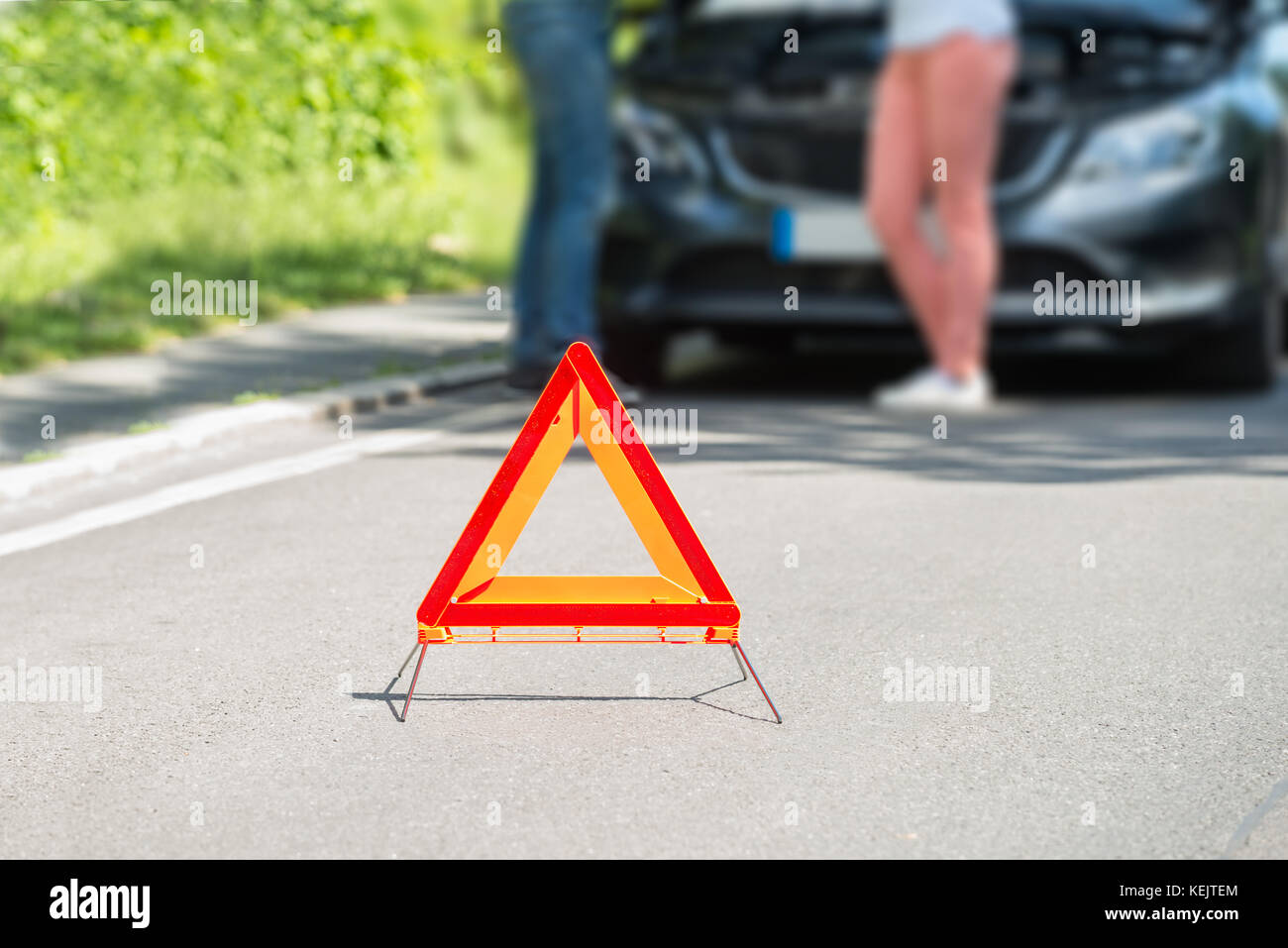 Close-up Of A Triangular Warning Sign With Couple Standing In Front Of Broken Down Car - Stock Image