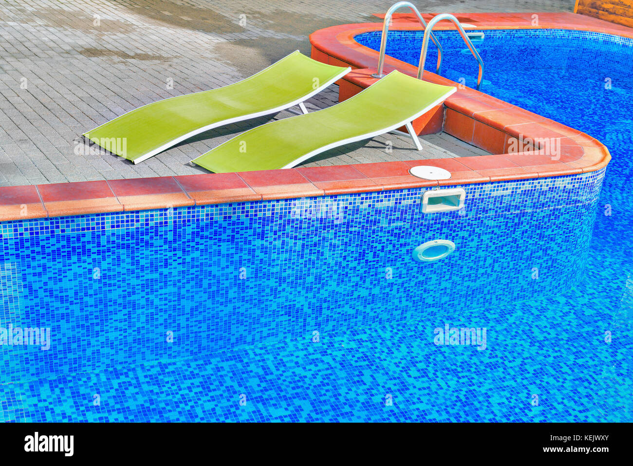 Two chaise-longues by the swimming pool on the hotel territory. - Stock Image
