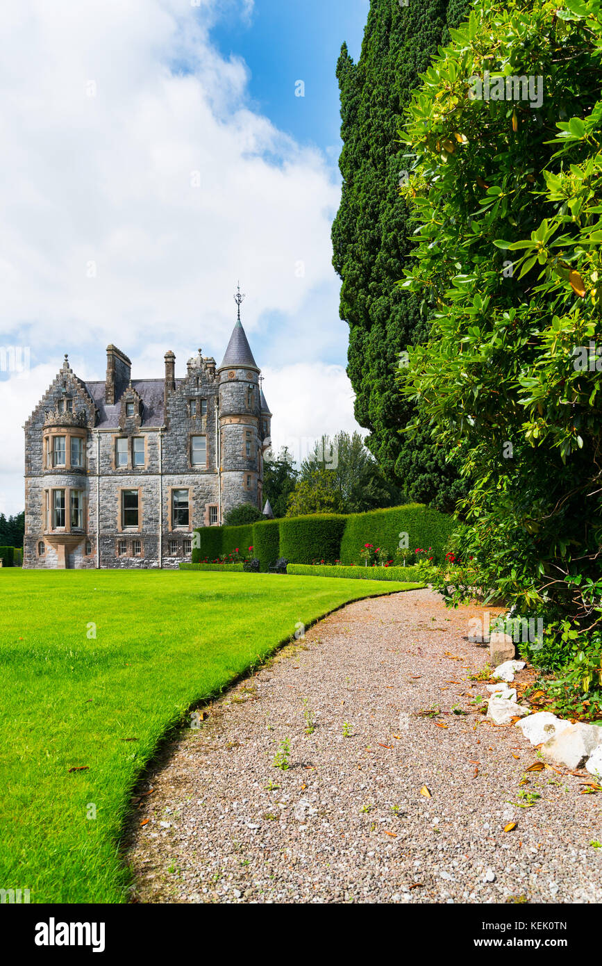 Pathway leading along side of large green lawn and tall trees to beautiful old castle - Stock Image