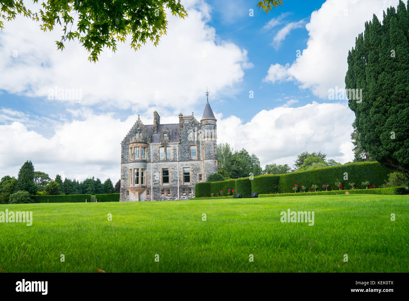 Large green lawn and gardens in front of distant stone castle under blue sky with large white clouds. - Stock Image