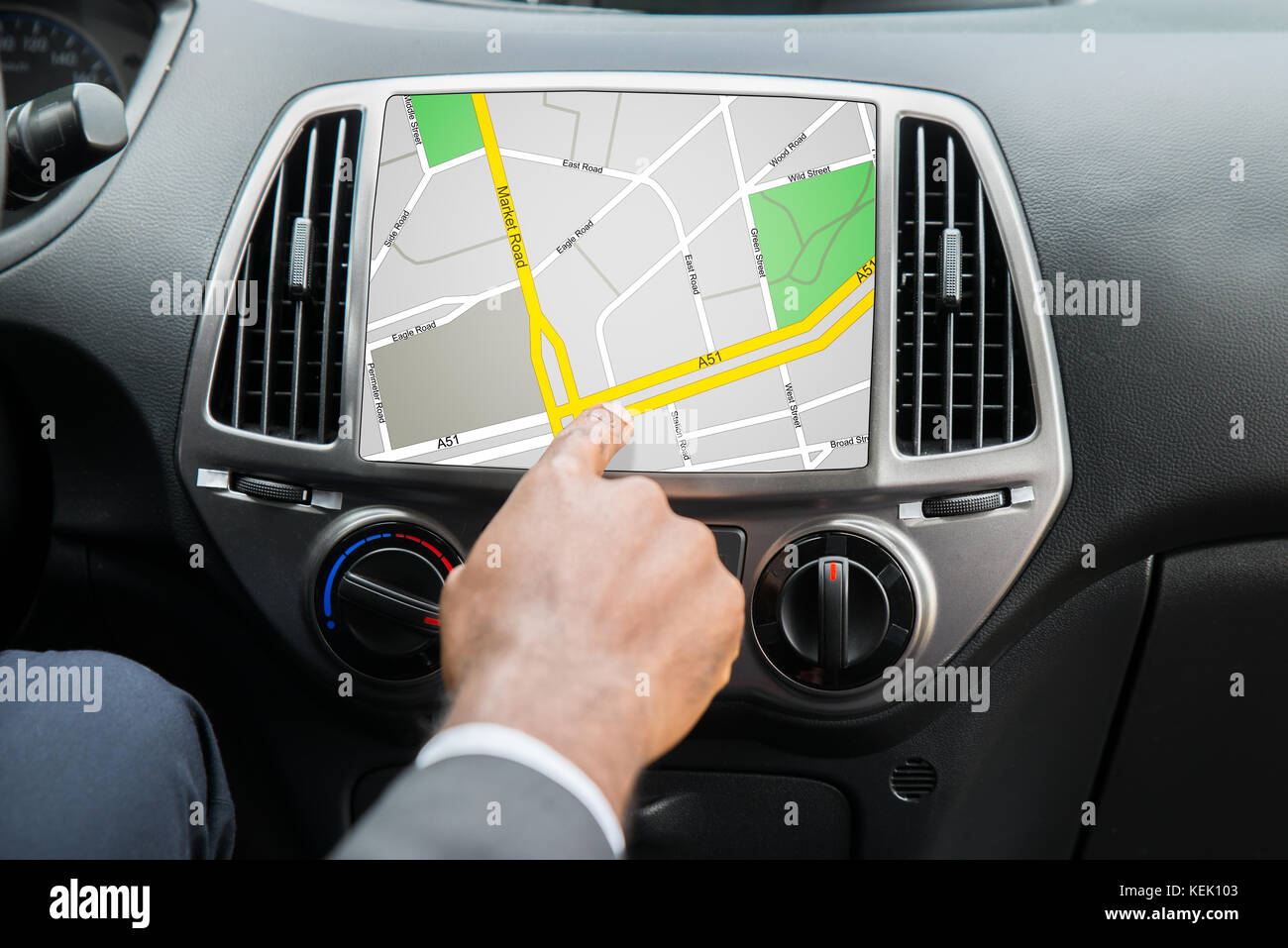 Close-up Of Person's Hand Using GPS Navigation System In Car Stock Photo