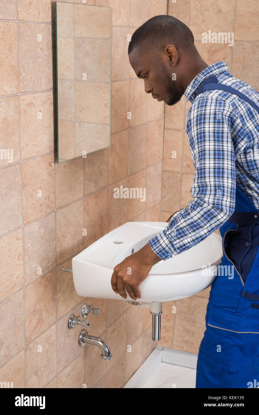 Side View Of Young African Male Plumber Fixing Sink In Bathroom ...