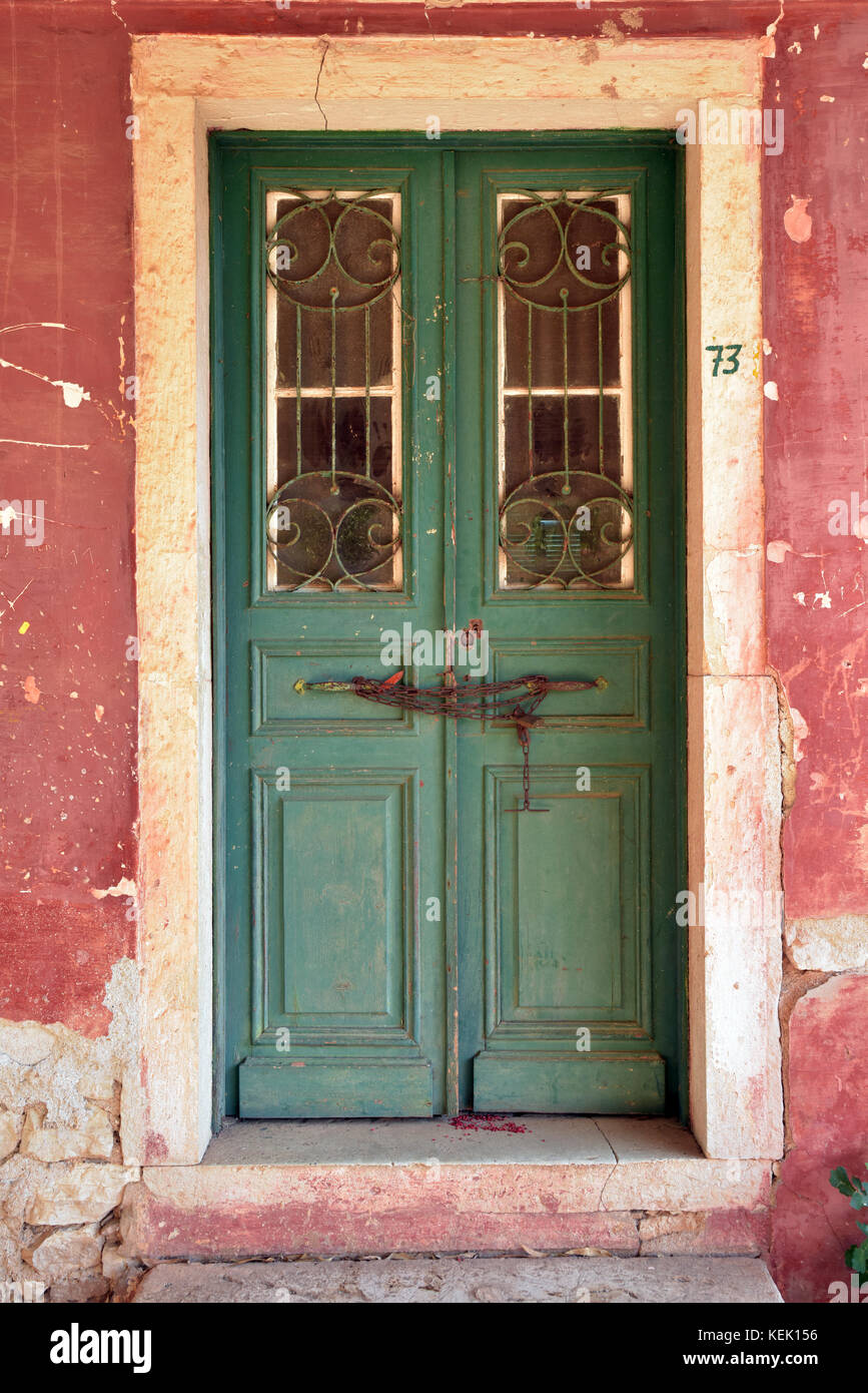 an old green painted door with a terracotta surround and glazed panels with distressed paintwork and shabby chic - Stock Image