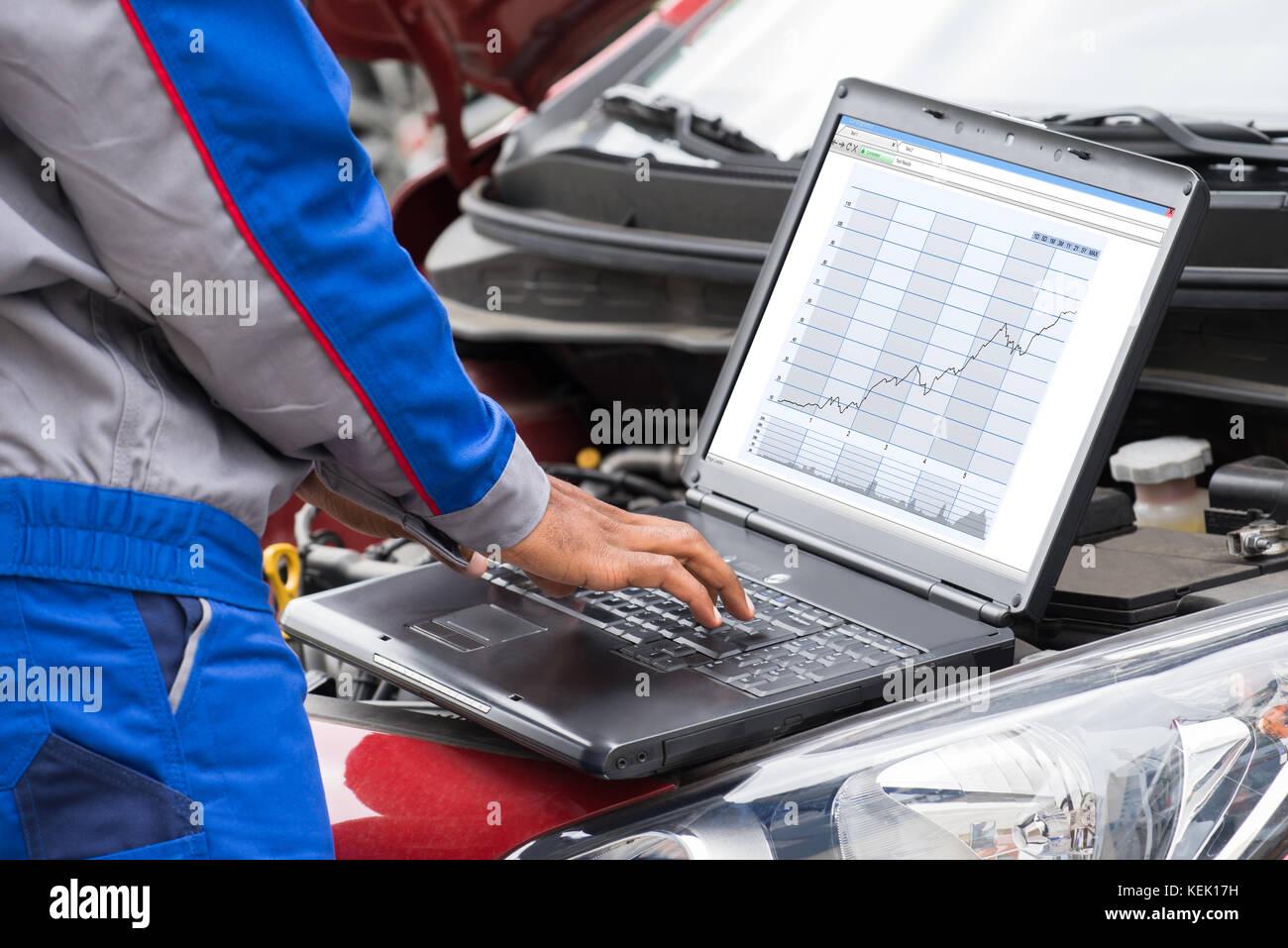 Close-up Of Male Mechanic Using Laptop For Examining Car Engine - Stock Image
