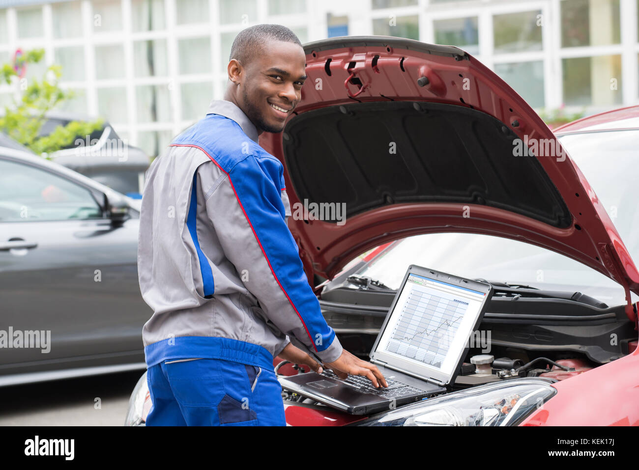 young happy mechanic using laptop in front of open car engine - stock image
