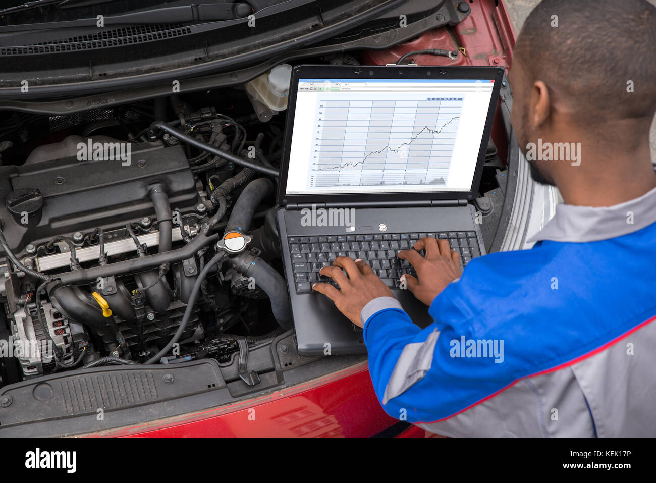 Young Male Mechanic Using Laptop While Examining Car Engine - Stock Image