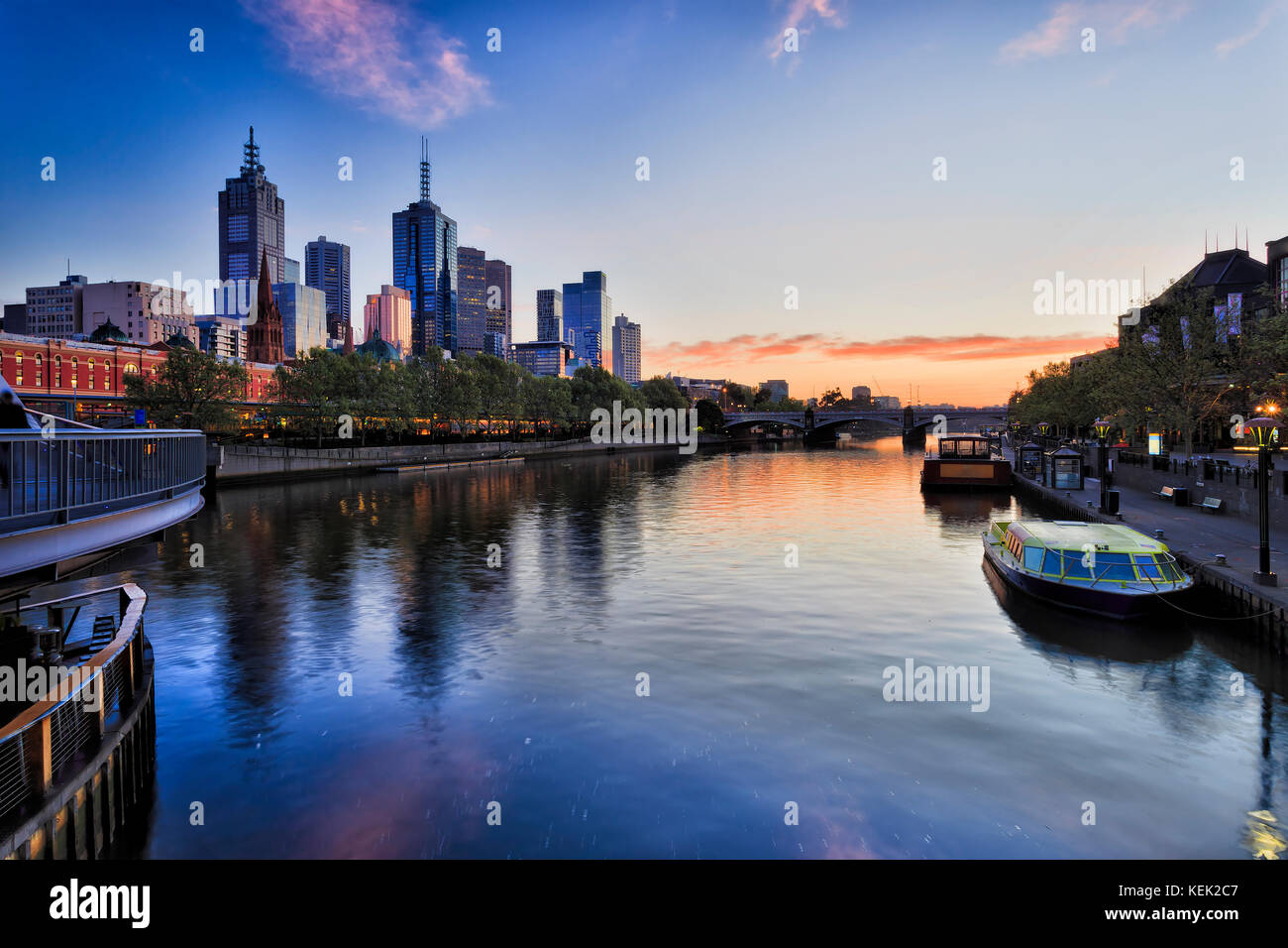 Melbourne city CBD on waterfront along Yarra river with Flinders station and Prince bridge at sunrise reflecting - Stock Image