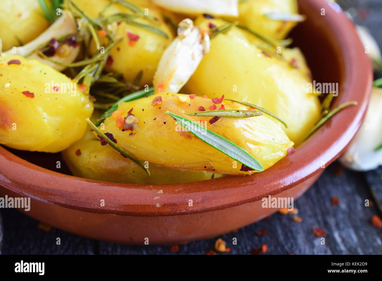 Oven cooked potato with rosemary, garlic, olive oil and mix of spices in a traditional ceramic bowl. Mediterranean Stock Photo