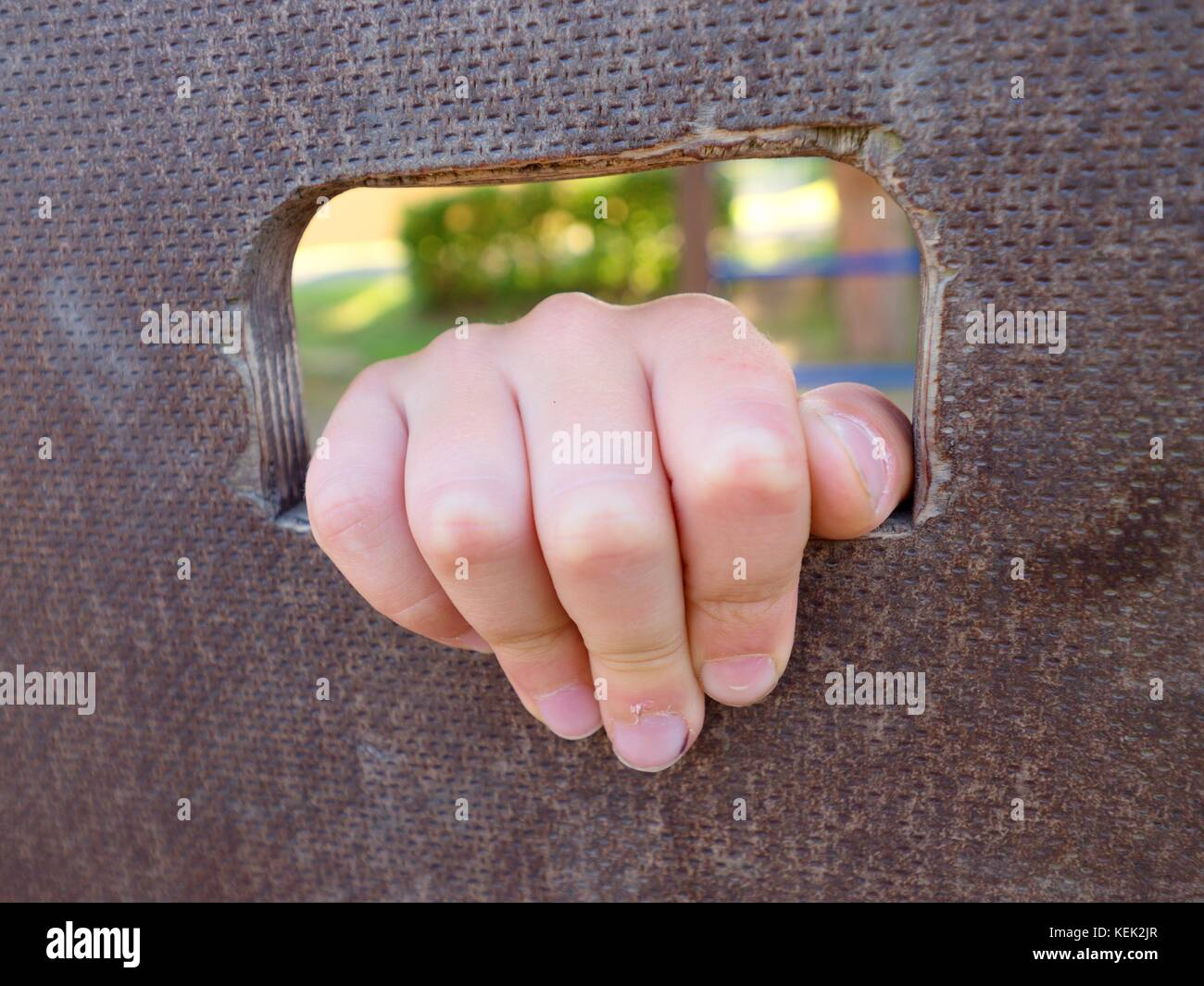 Children hand holds a hole on the wooden climbing wall. Short fingers hold through board ladder - Stock Image