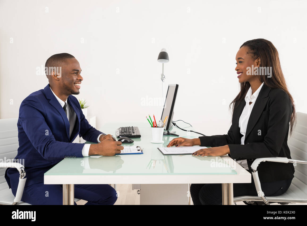Male Manager Interviewing A Young Female Applicant In Office - Stock Image