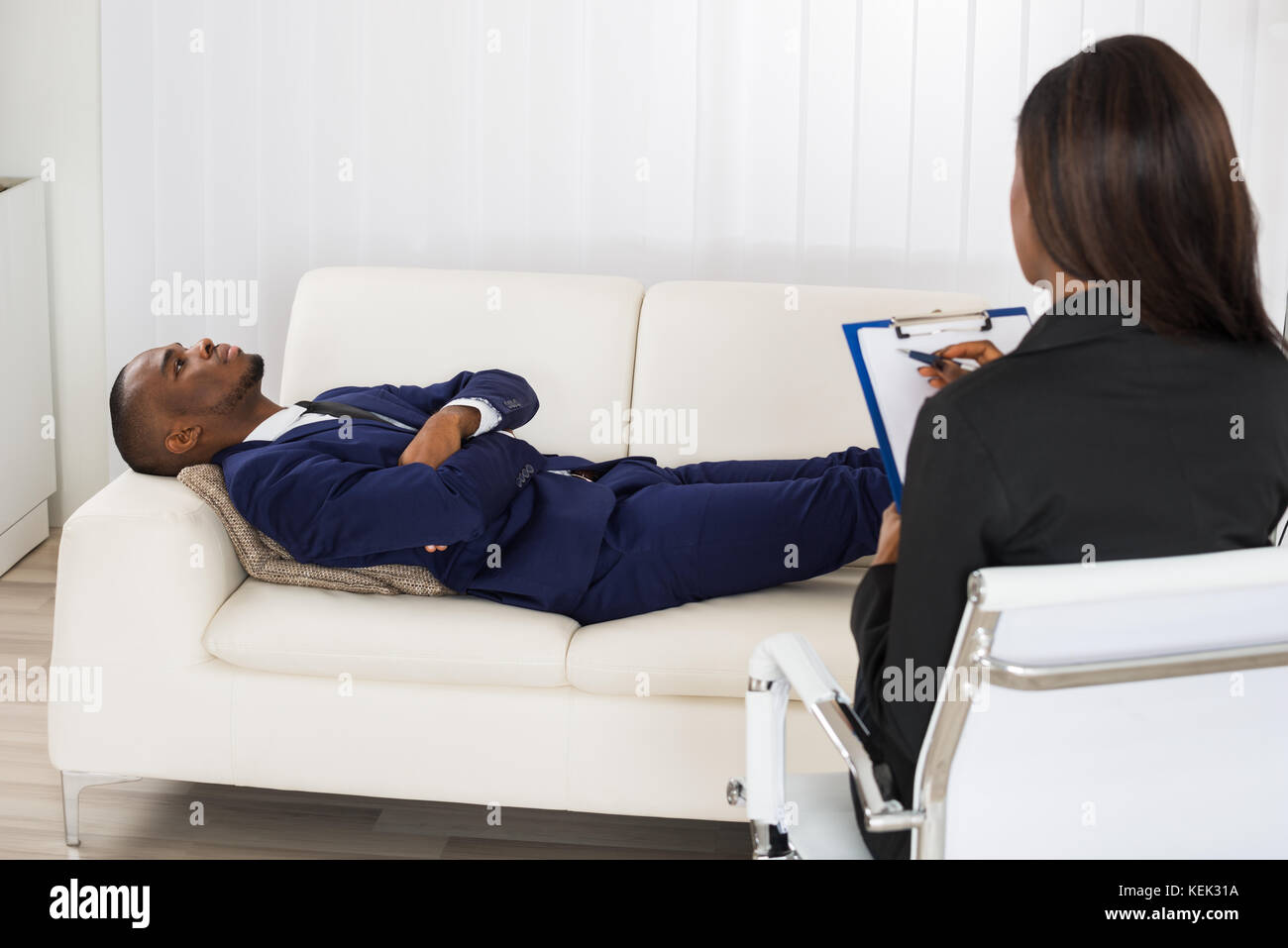 African American Man Laying On Couch In Front Of Psychiatrist With Clipboard - Stock Image