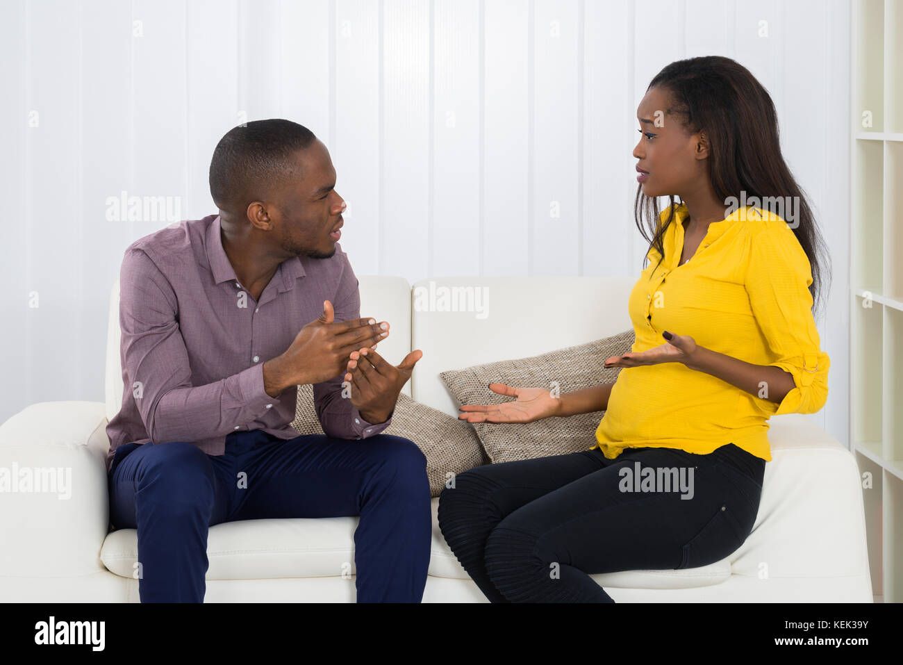 Young Couple Sitting On Sofa Quarreling With Each Other - Stock Image