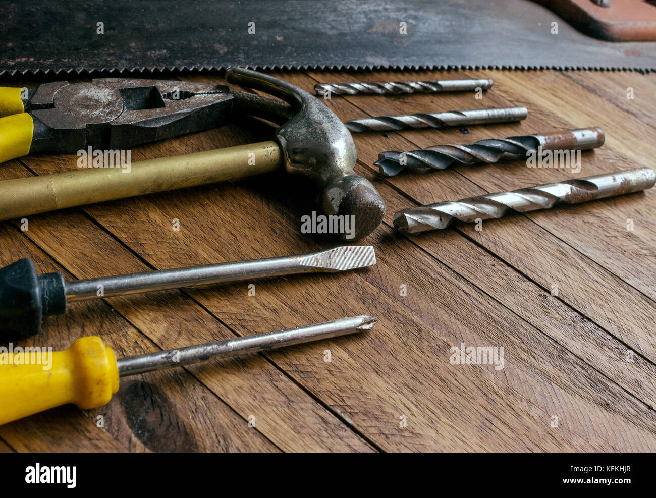 Rusty and old used carpentry and garage tools on a light brown wood background, showing varied tools,with metal pliers and saw,metal drill bits,hammer Stock Photo