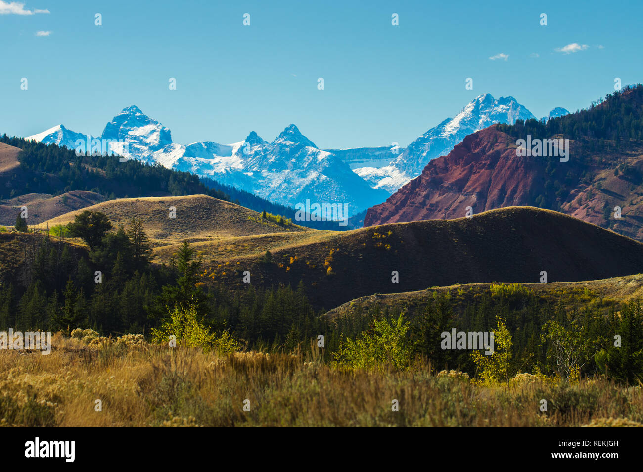 The diverse Wyoming landscape is revealed in colorful layers of Earth with the ever present Grand Teton Mountains, - Stock Image