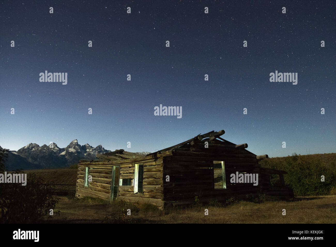 An old derelict homesteader cabin home sits under a lonely starlit sky with the Grand Teton mountains of Wyoming Stock Photo