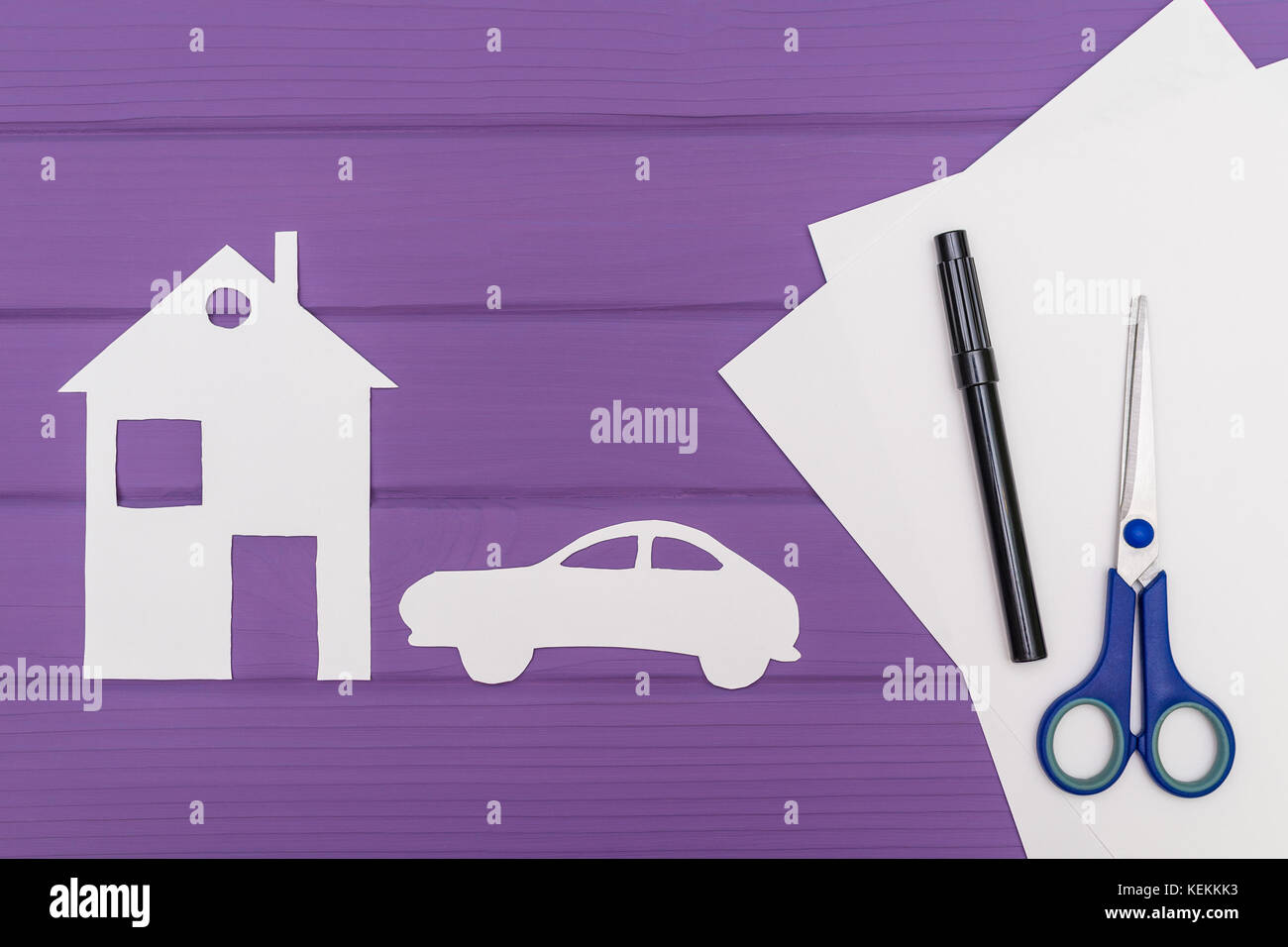 The silhouettes cut out of paper of car and house, scissors and marker near on a white sheet of paper on purple - Stock Image