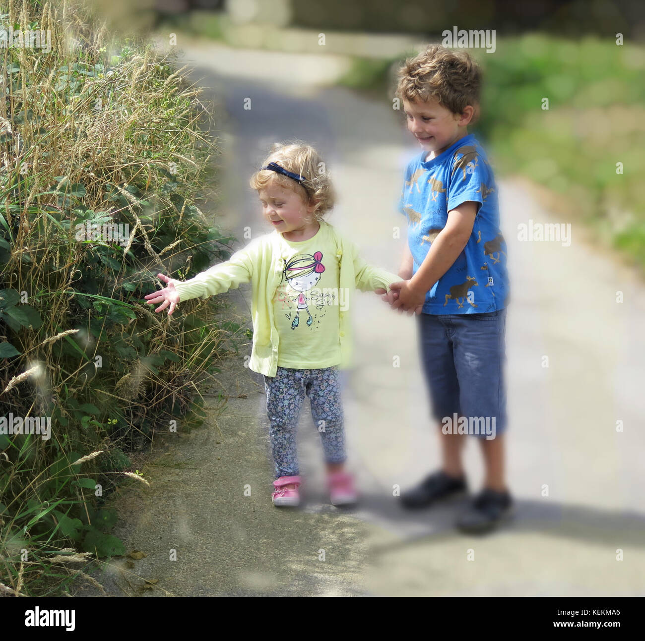 Young boy and girl holding hands out walking in the park - Stock Image
