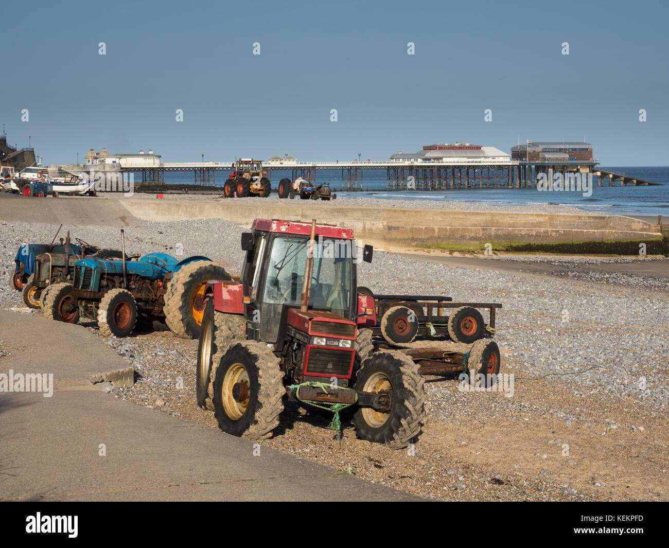 Fishermens tractors on the beach at sunny Cromer, Norfolk, England - Stock Image