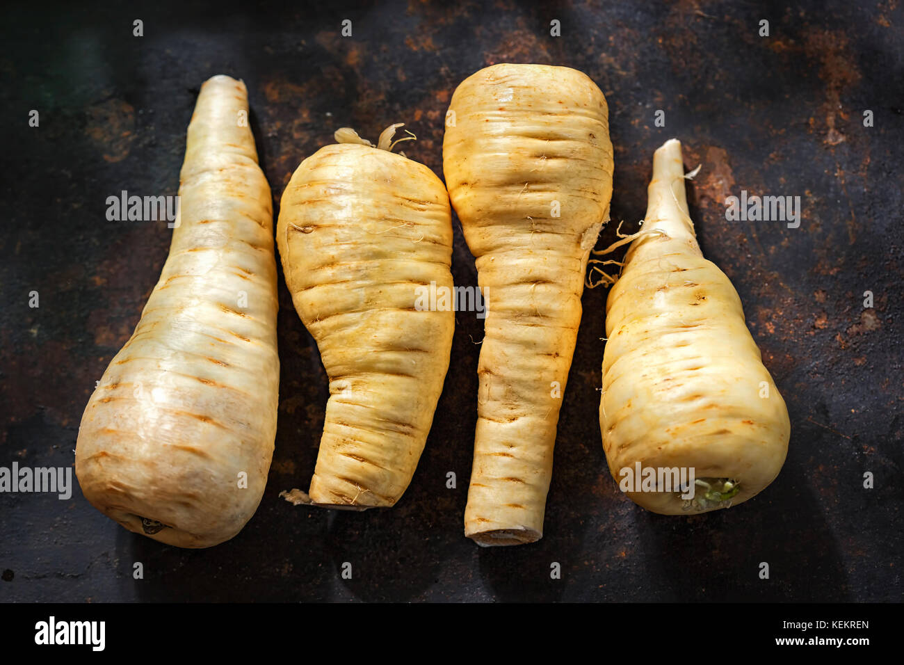 Raw parsnip roots on black surface - Stock Image