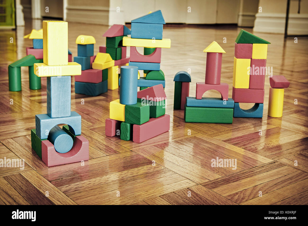 Colorful wooden building blocks on hardwood floor. Stock Photo
