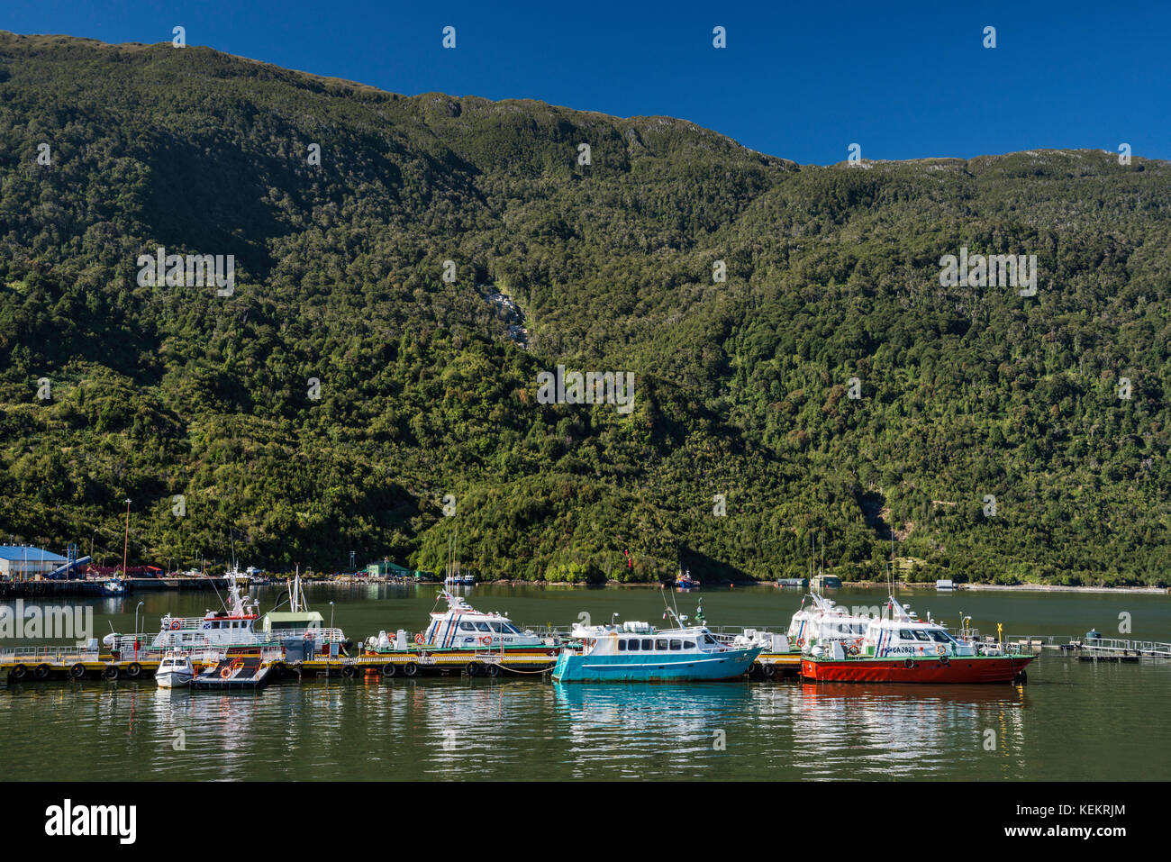 Boats moored in port of Puerto Chacabuco, Aisen Fjord, Valdivian temperate rainforest, Aysen Region, Patagonia, - Stock Image