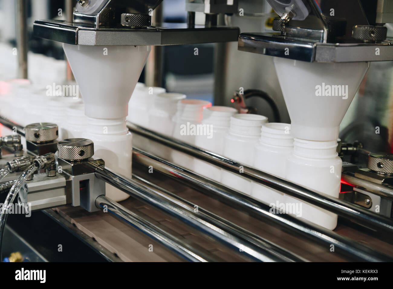 white plastic bottles on the production line of the conveyor at filling machine in the factory. selective focus. - Stock Image
