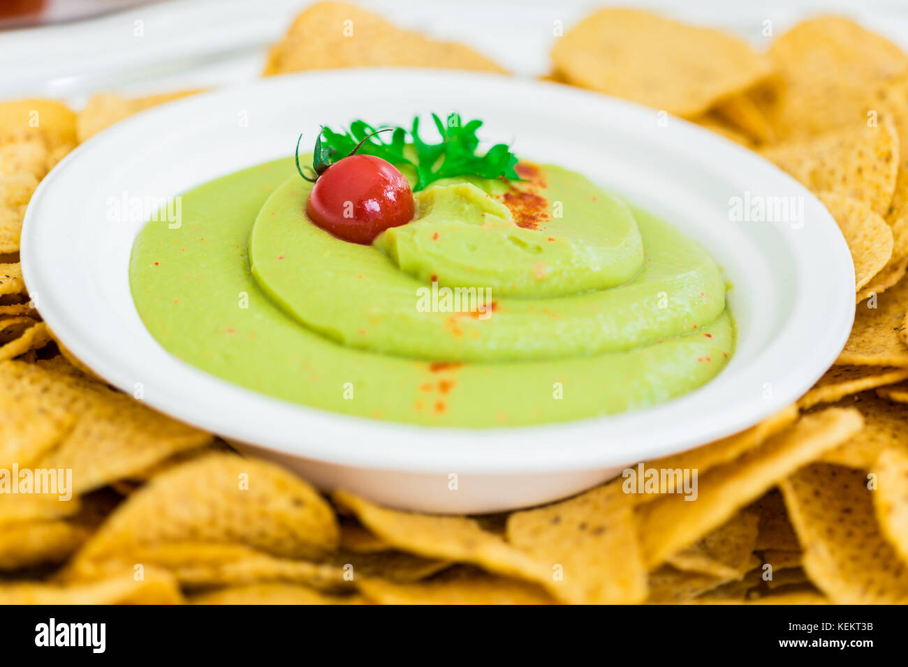 A plate of Guacamole with tortilla chips. This recipe is typically Mexican. - Stock Image