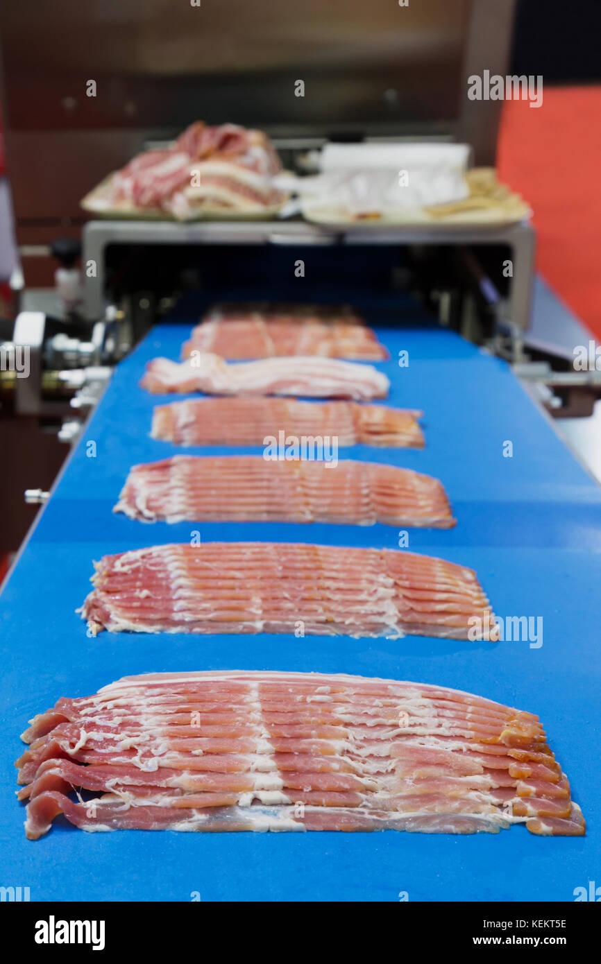 bacons slicing on the conveyor belt of meat slicing machinery industrial ready to fill in the packaging of meat - Stock Image