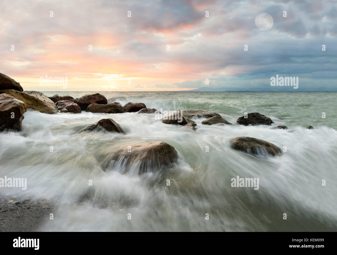 Ocean moon waves sunset is a surreal abstract seascape with waves rushing over rocks as the sun sets on the ocean Stock Photo