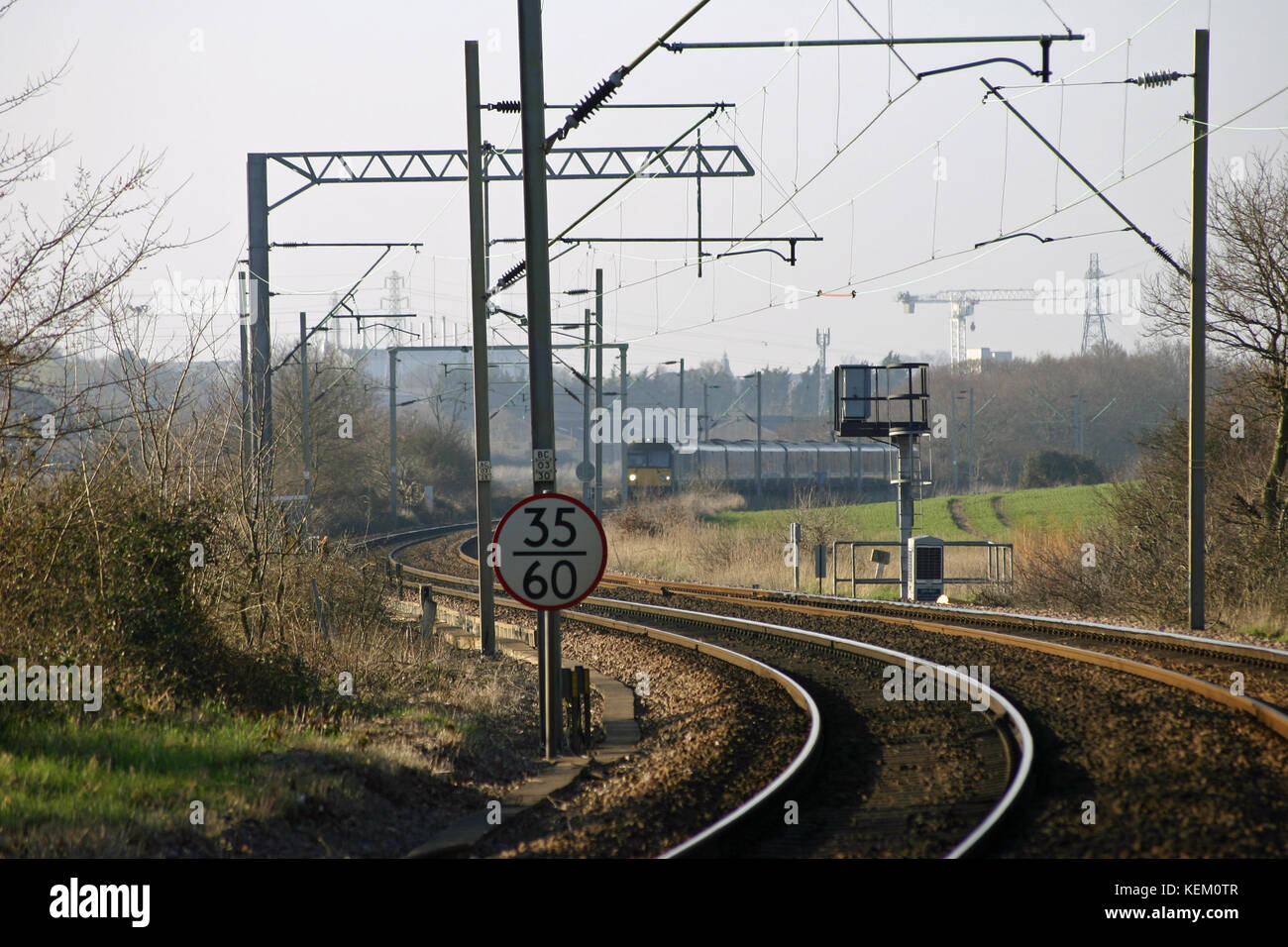 Curved local railway line with electric overhead cables and train in the distance. Background of trees, hedges and - Stock Image