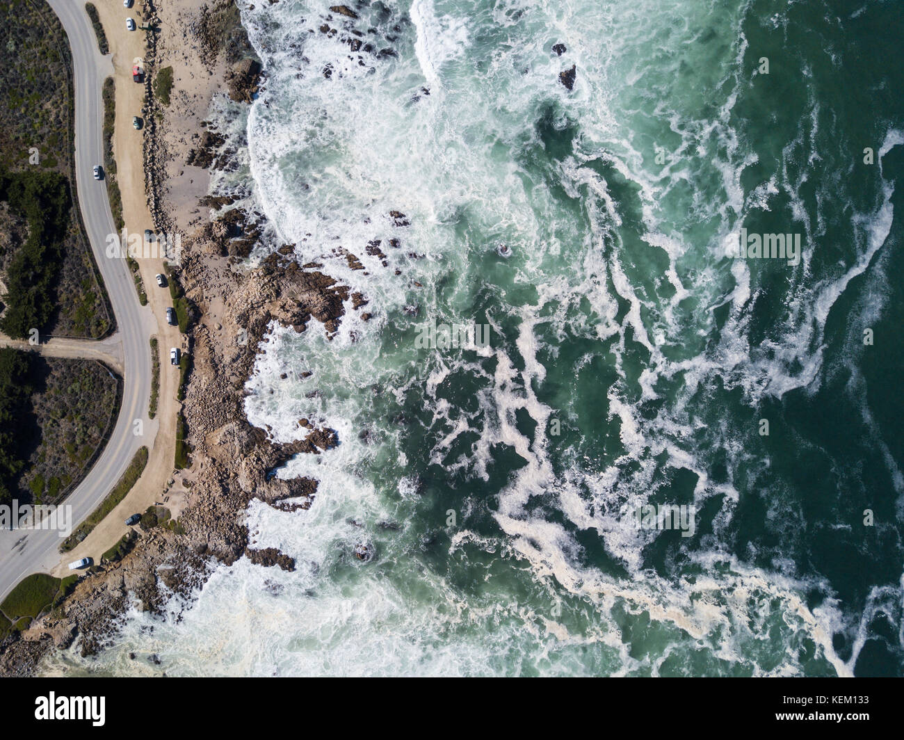 The Pacific Ocean washes against the rocky and scenic coastline of the Monterey peninsula in California. - Stock Image