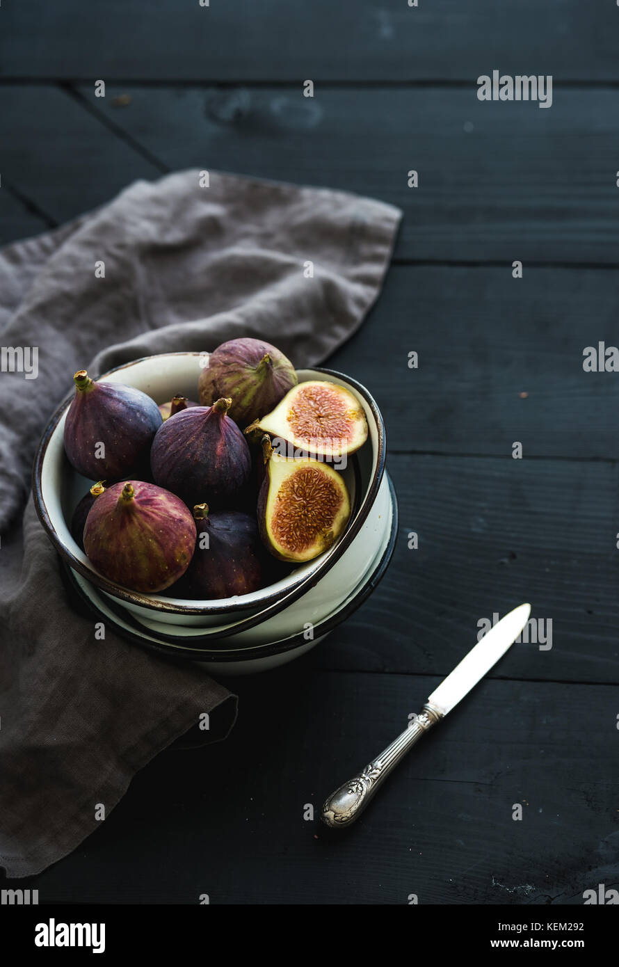 Rustic metal bowl of fresh figs on dark background, top view, selective focus - Stock Image