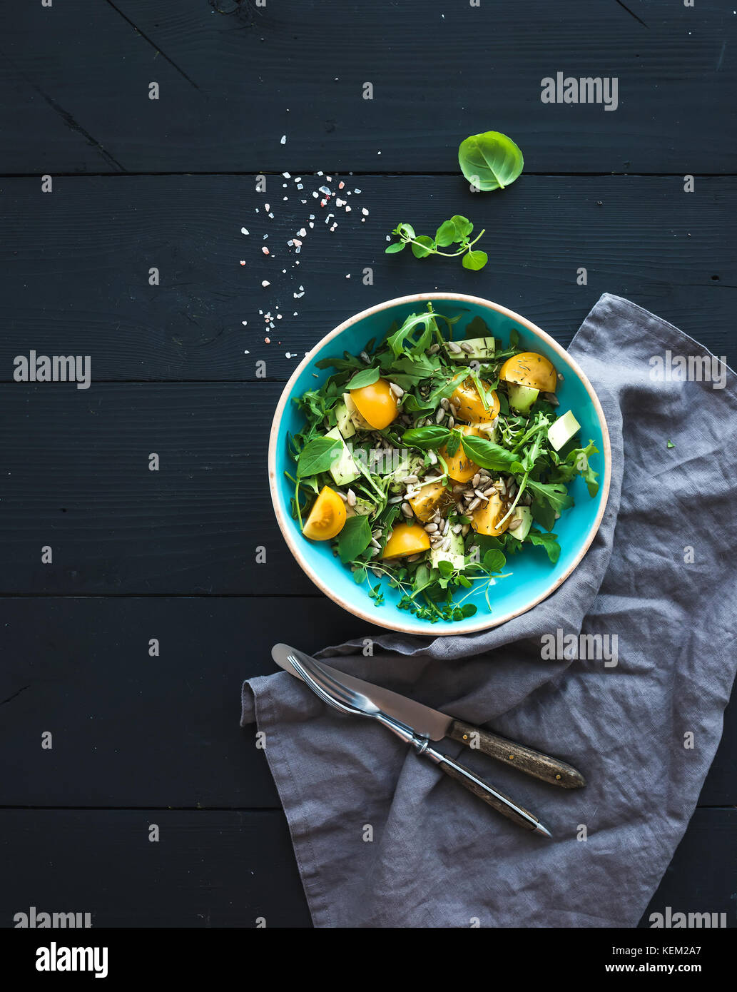Bowl of green salad with avocado, arugula, cherry tomatoes and sunflower seeds, grilled bred slices, fresh herbs - Stock Image
