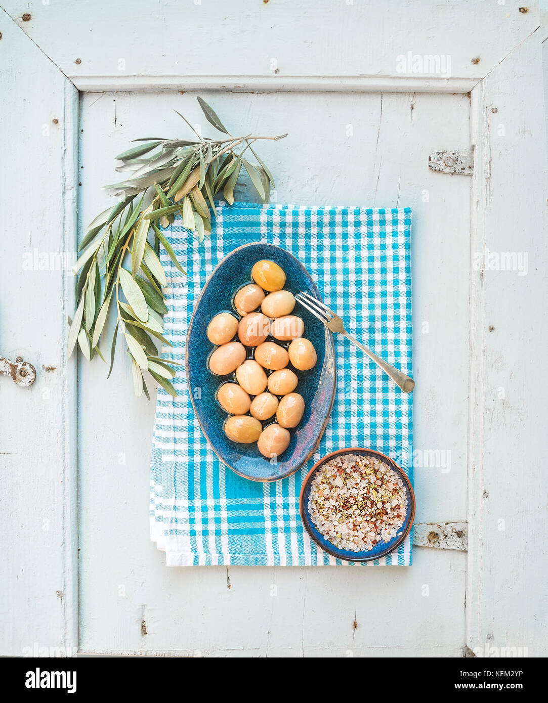 Green big olives in blue ceramic plate with tree branch and spices on kitchen towel over light blue background, - Stock Image