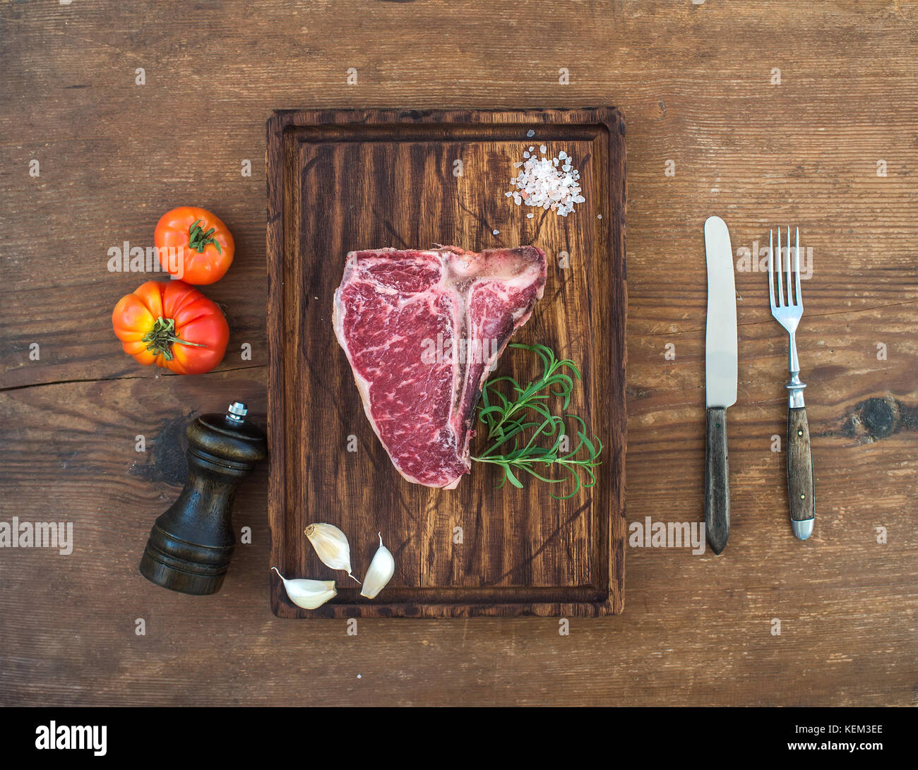 Raw fresh meat t-bone steak with garlic cloves, tomatoes, rosemary and salt on serving board over rustic wooden Stock Photo