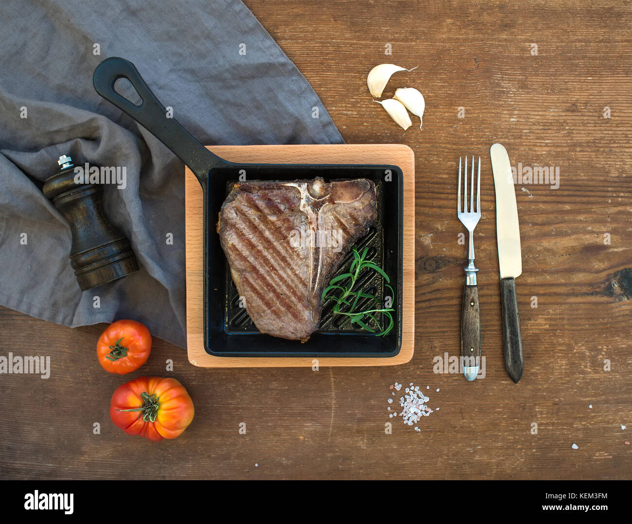 Cooked meat t-bone steak with garlic cloves, tomatoes, rosemary, pepper and salt in small cooking pan over rustic - Stock Image