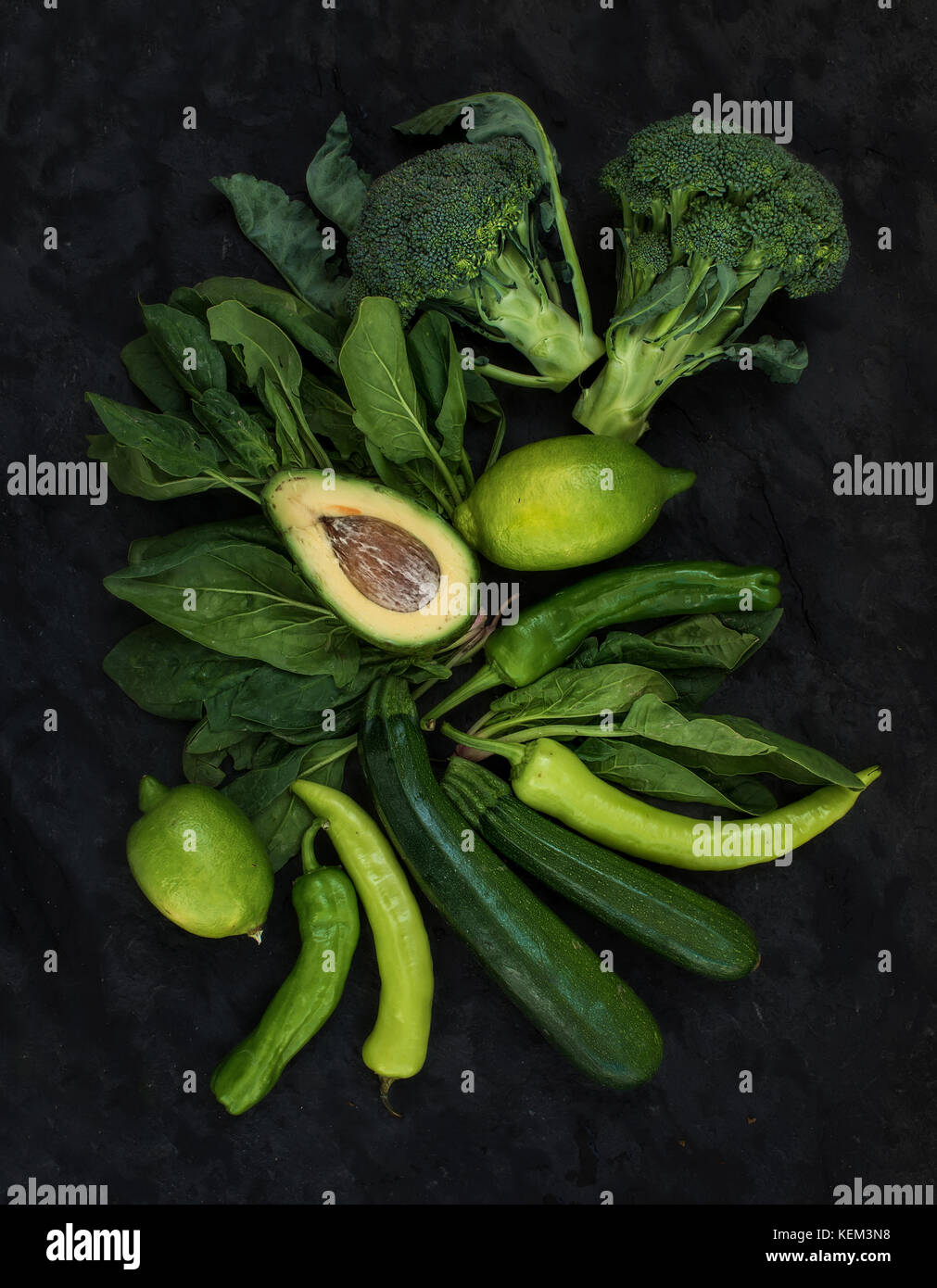 Raw green vegetables set. Broccoli, avocado, pepper, spinach, lime on dark stone background, top view - Stock Image