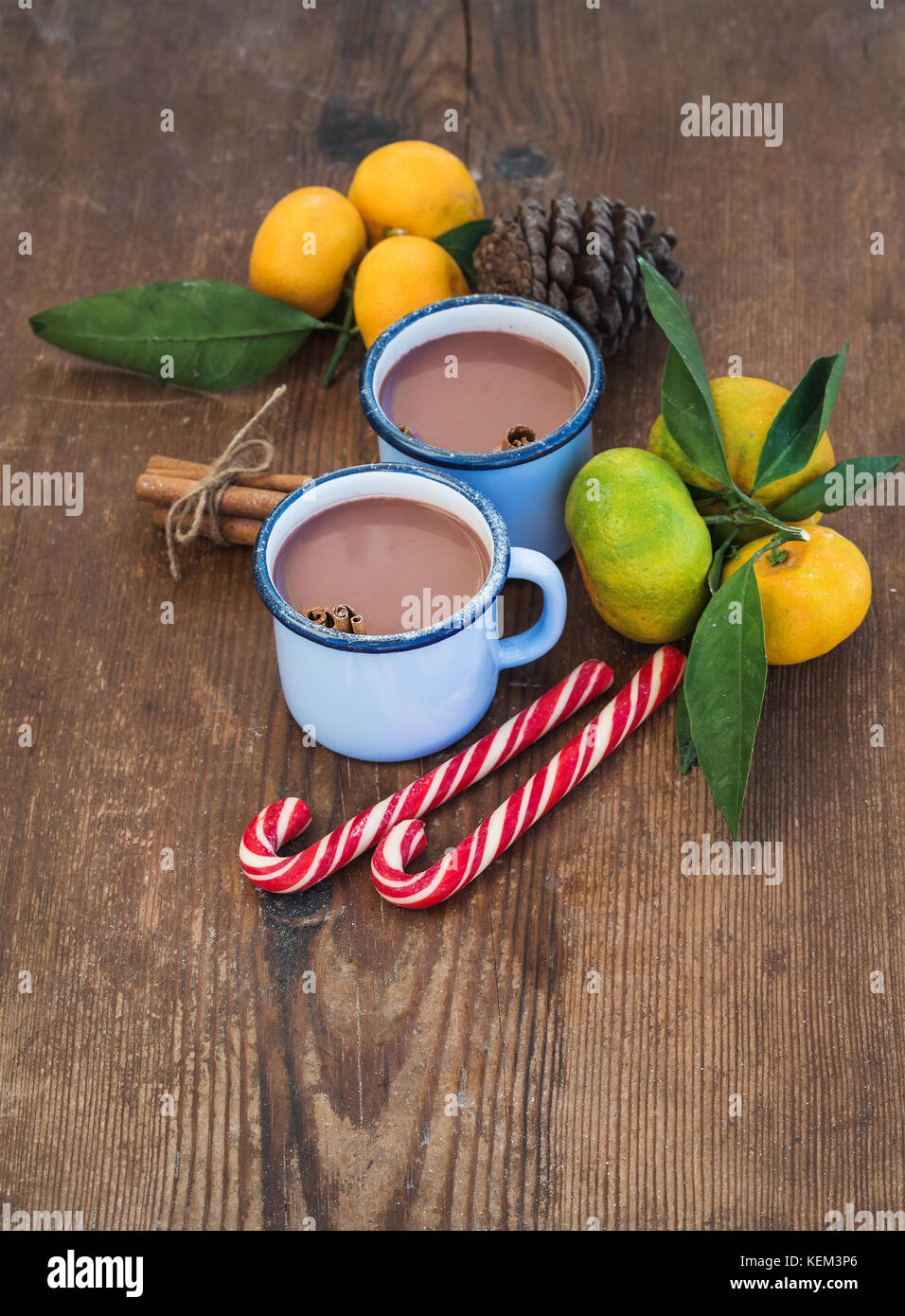 Hot chocolate in enamel metal mugs, fresh mandarines, cinnamon sticks, pine cone and candy canes over rustic wooden - Stock Image