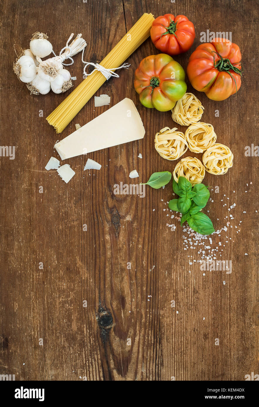 Ingredients for cooking pasta. Spaghetti, tagliatelle, garlic, Parmesan cheese, tomatoes and fresh basil on rustic - Stock Image