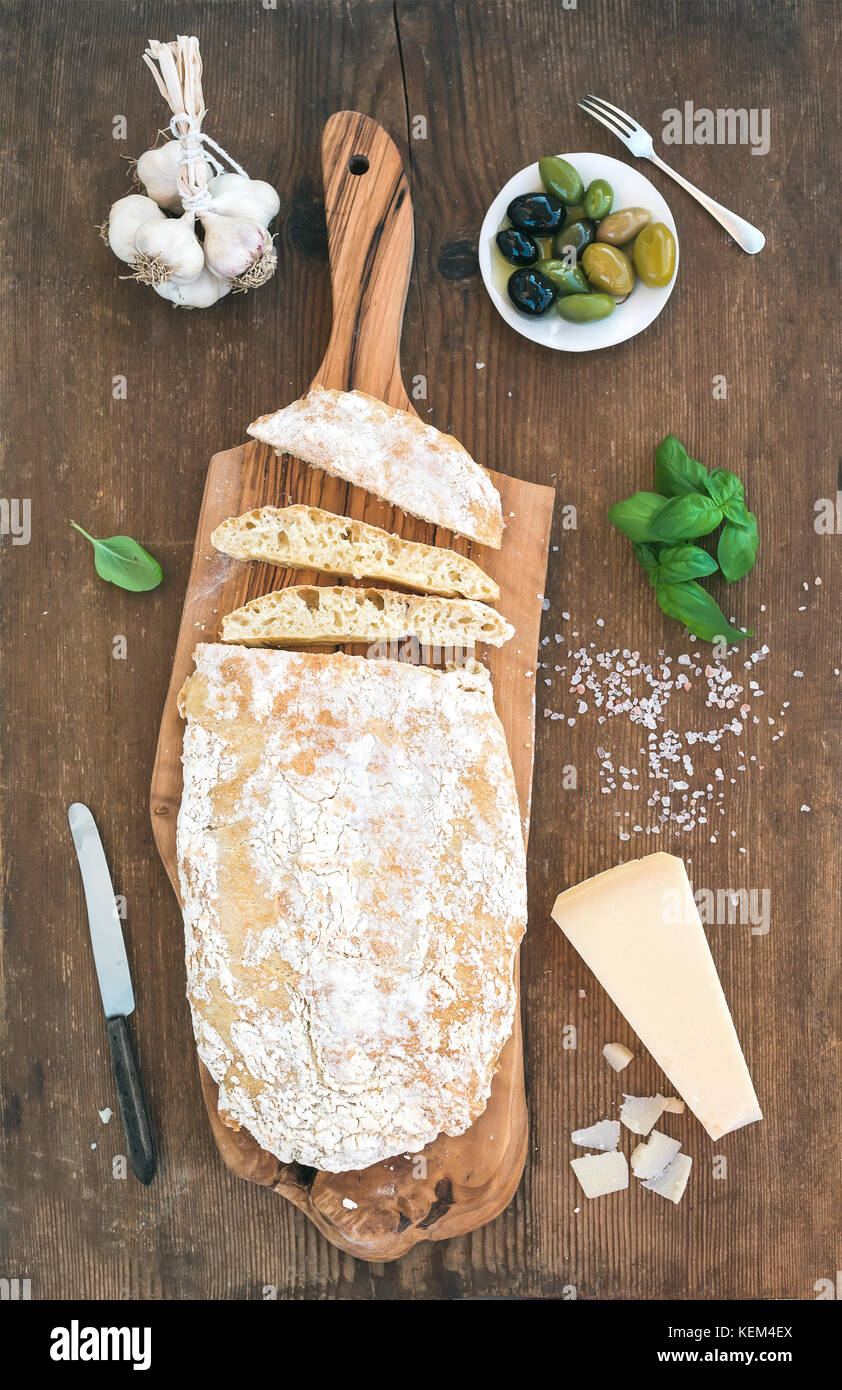 Freshly baked ciabatta bread with garlic, mediterranean olives, basil and Parmesan cheese on serving board over - Stock Image