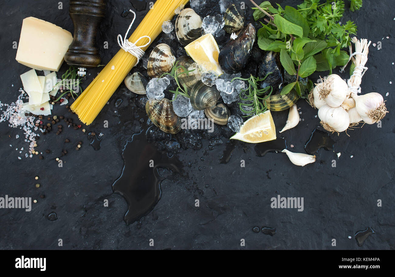 Ingredients for cooking Spaghetti vongole. Clams on chipped ice, raw pasta, Parmesan cheese, garlic, parsley and - Stock Image