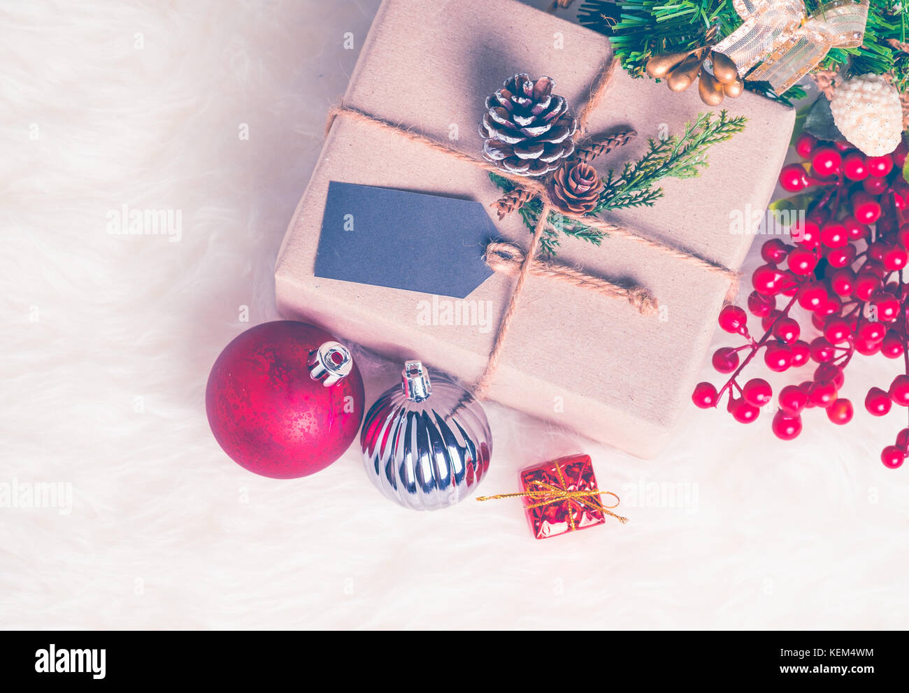 Brown paper craft warped on present box with label tag decorate with pine cone and christmas ball under xmas tree,Gift - Stock Image