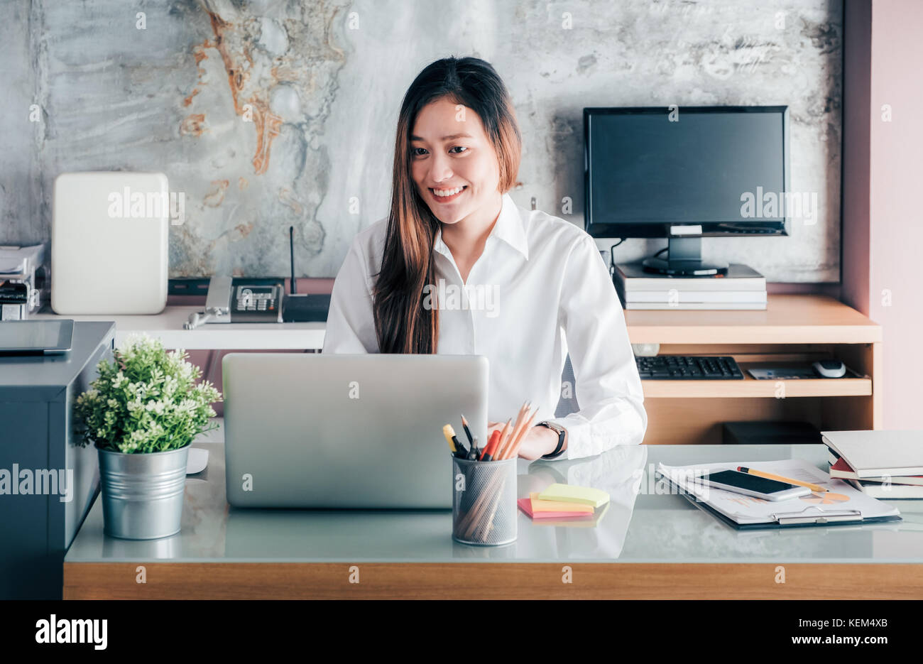 Asia businesswoman looking at laptop computer and smiling face and rest chin on hand with happy emotion from good - Stock Image