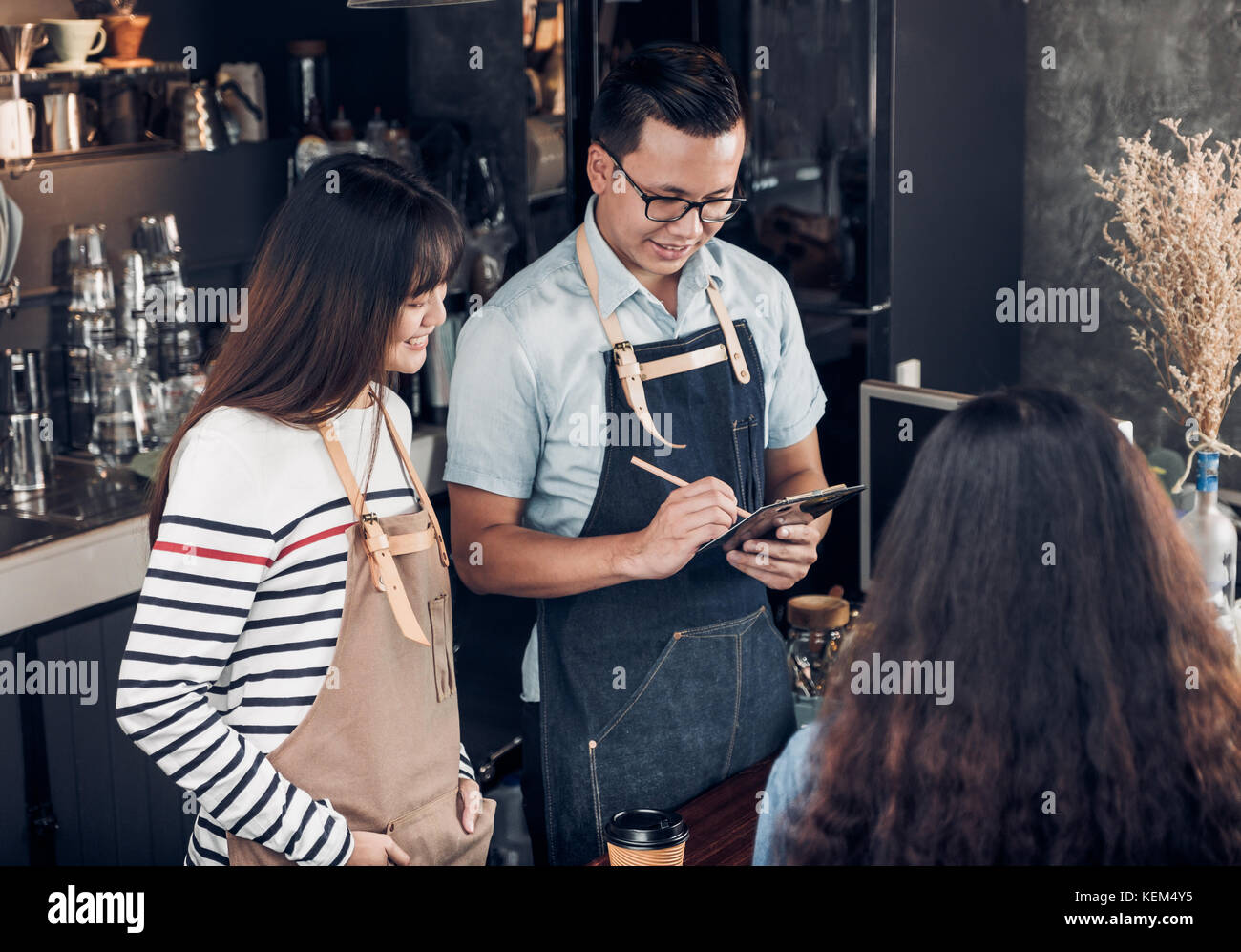 Asia Barista waiter take order from customer in coffee shop,Two cafe owner writing drink order at counter bar,Food - Stock Image