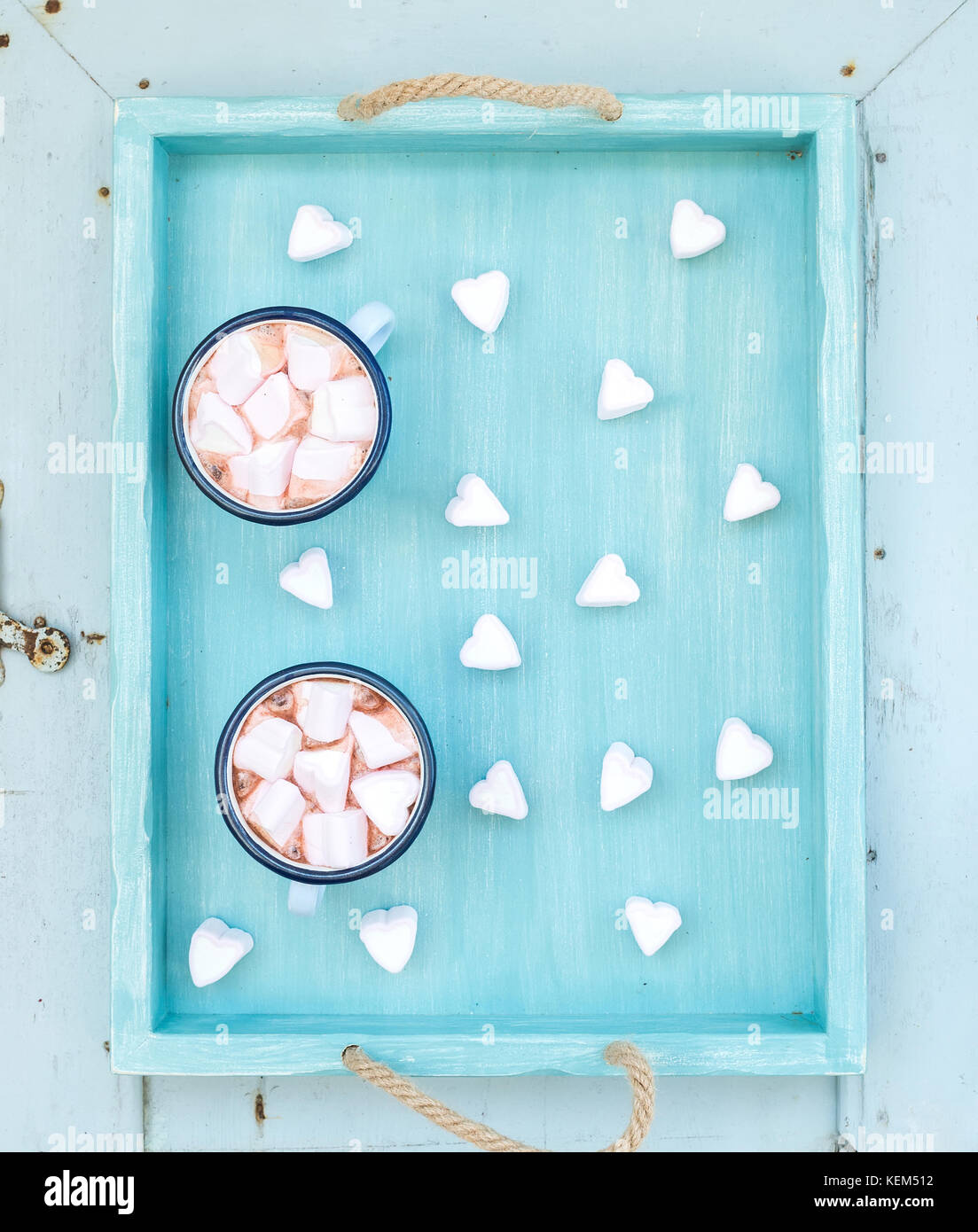 Saint Valentine's holiday greeting set. Hot chocolate and heart shaped marshmallows in old enamel mugs on turquoise - Stock Image