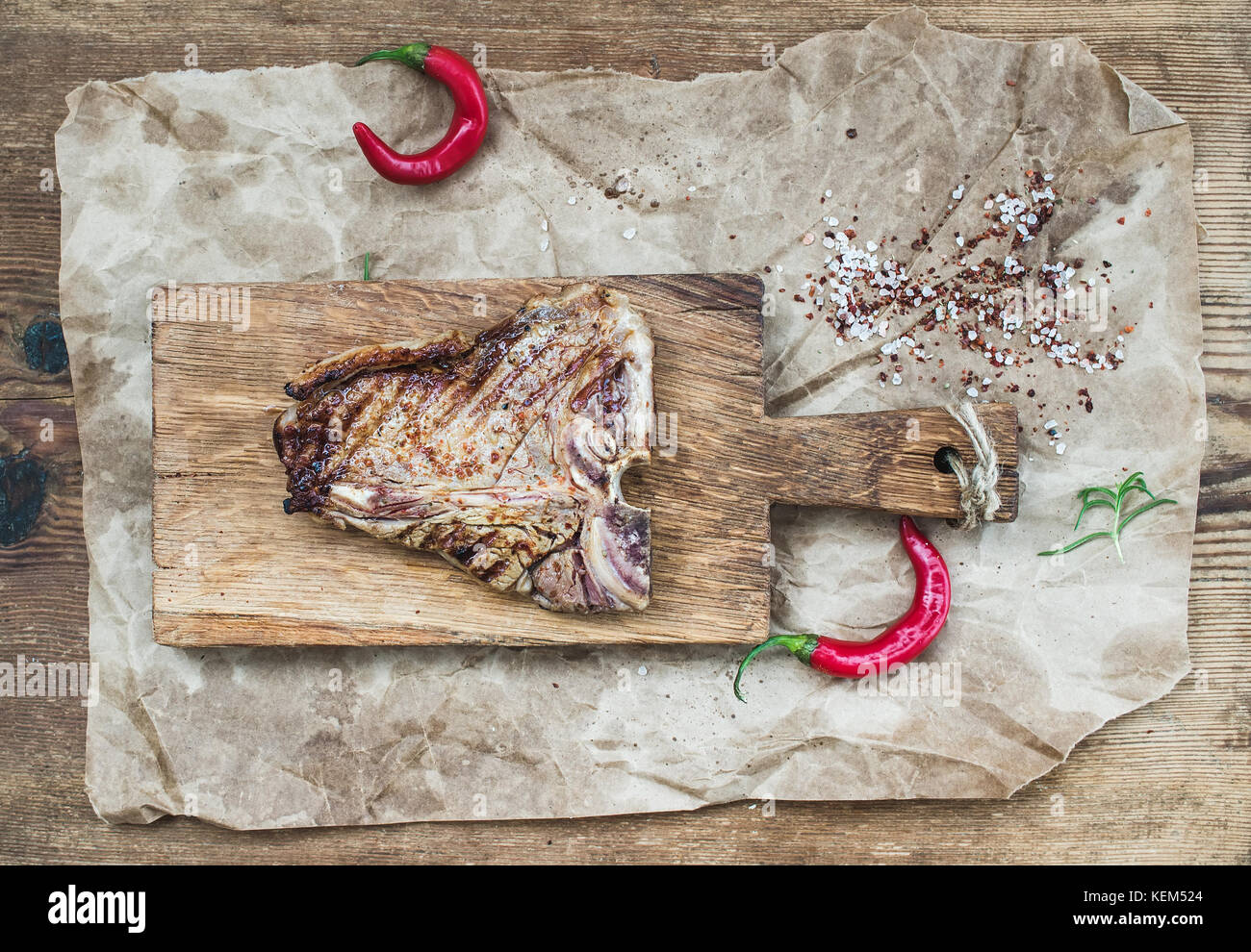 Cooked meat t-bone steak on serving board with red chili peppers Stock Photo