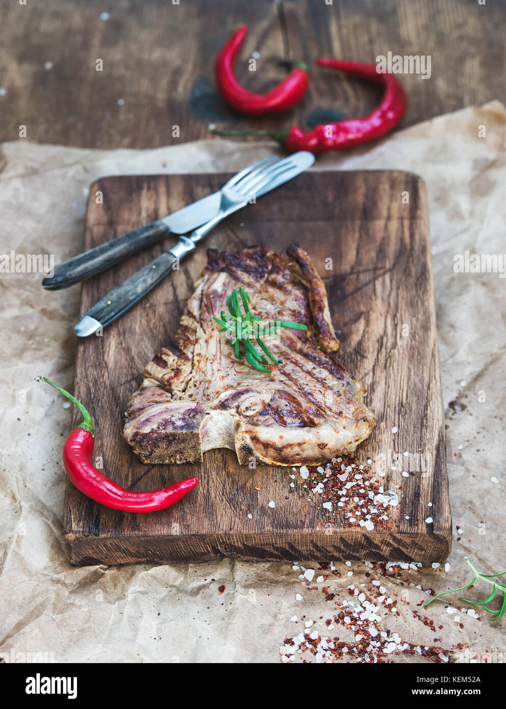 Cooked meat t-bone steak on serving board with red chili peppers, spices and fresh rosemary over oily craft paper, Stock Photo