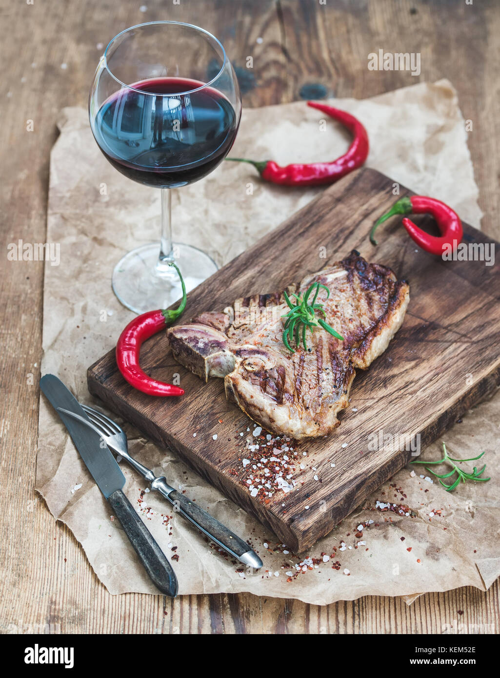 Cooked meat t-bone steak on serving board with roasted tomatoes Stock Photo
