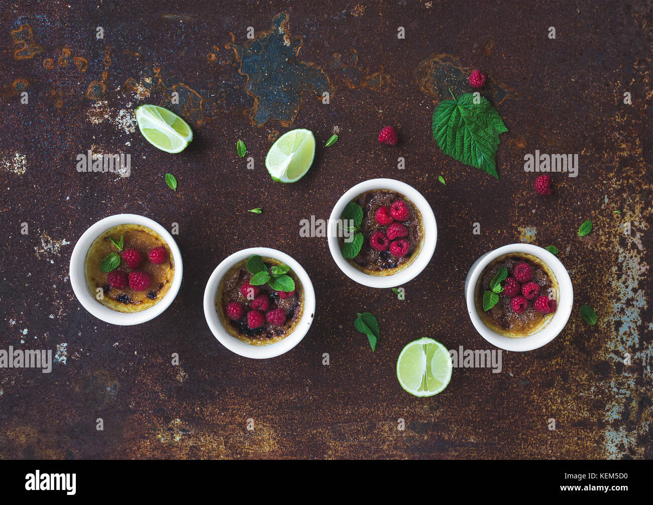 Creme brulees with raspberries and mint in white bowls over grunge metal backdrop. Top view - Stock Image